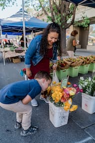 kid smelling flowers at a farmer's market