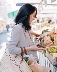 woman holding an artichoke while shopping at a farmer's market