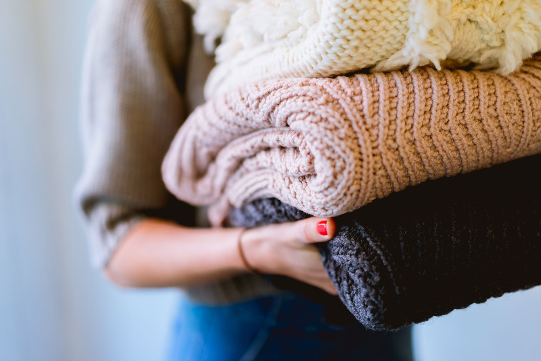 Close up of a woman carrying folded blankets