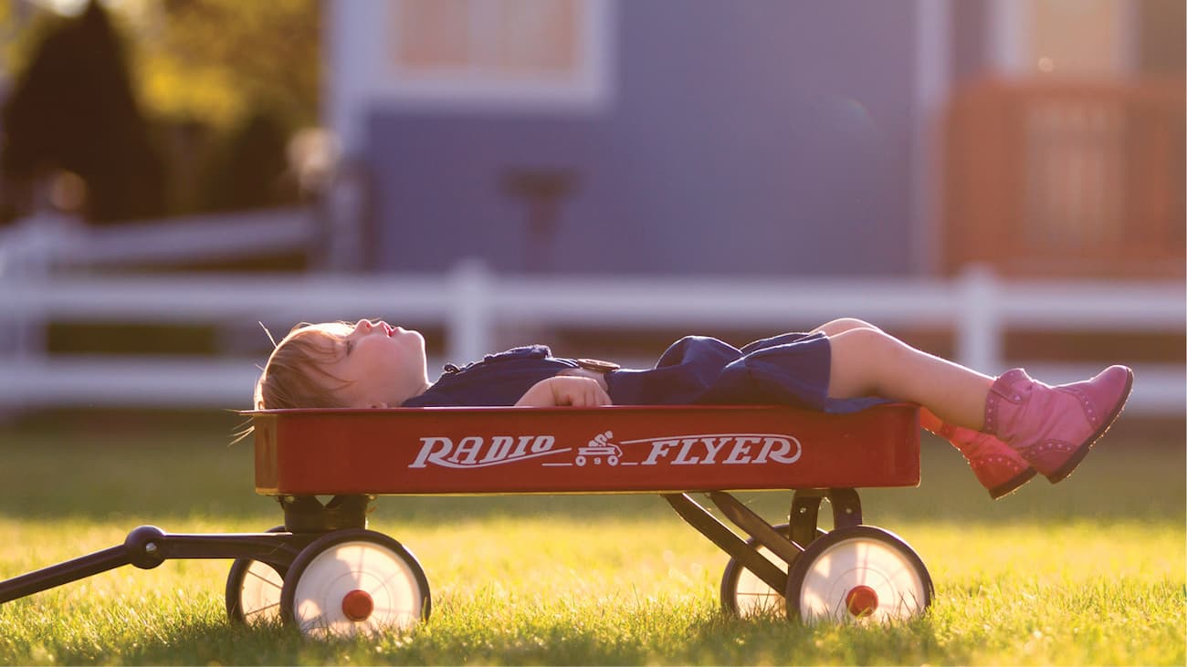 kid in red wagon on grass